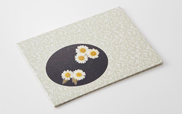 邪気払いの象徴とされる白菊の押し花を、洋更紗の文様がモダンな彩りを添えています