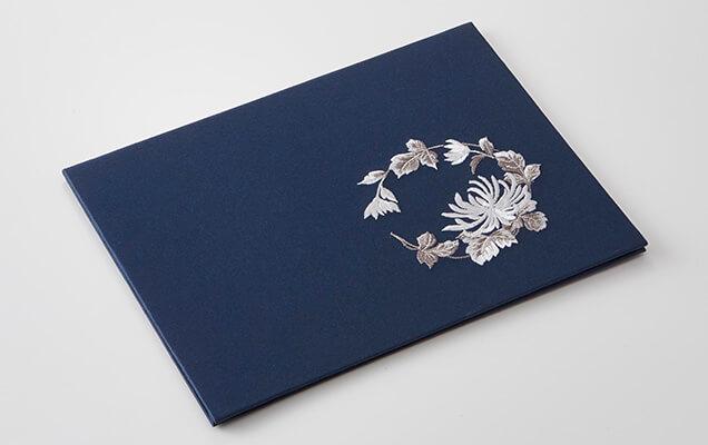 気品のある紺地に、邪気払いの象徴とされる菊花を薄墨と銀で表現しました