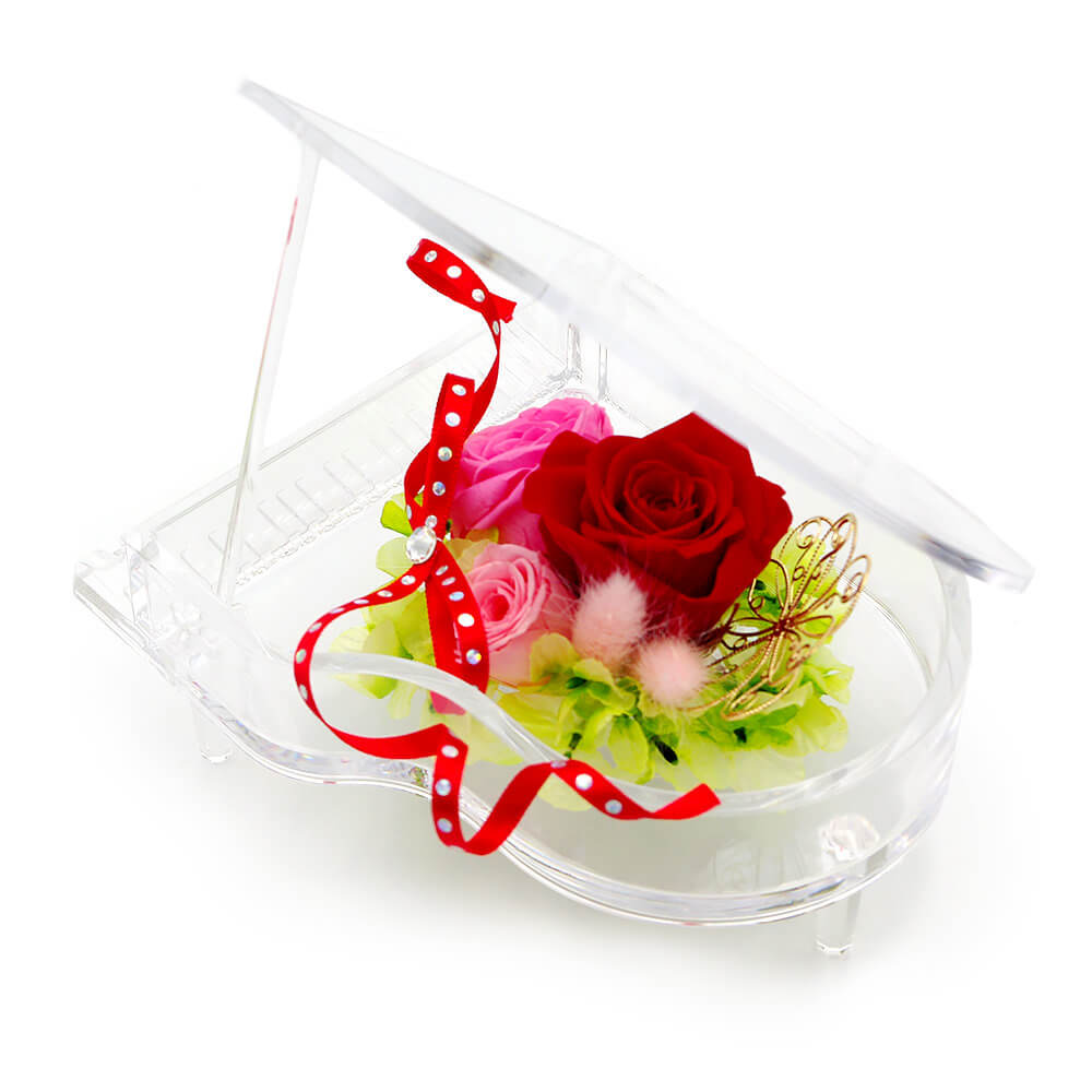 透明のグランドピアノに赤とピンクのバラをアレンジ