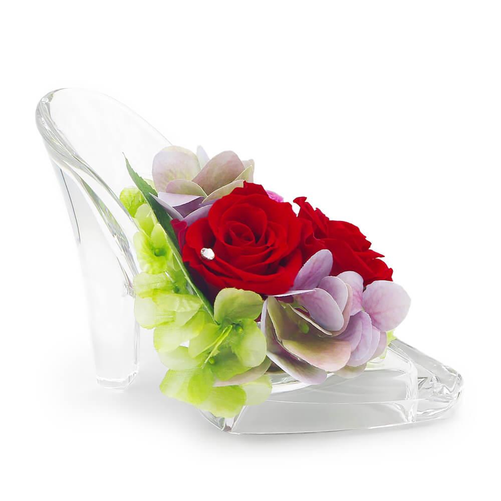 美しいクリアハイヒールに鮮やかな赤いバラ